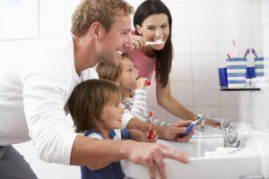 family brushing teeth as group