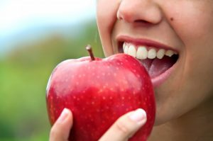 close up person about to eat apple