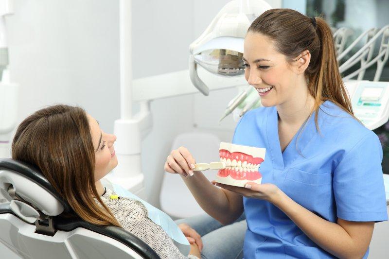 Dental hygienist smiling while demonstrating proper brushing technique